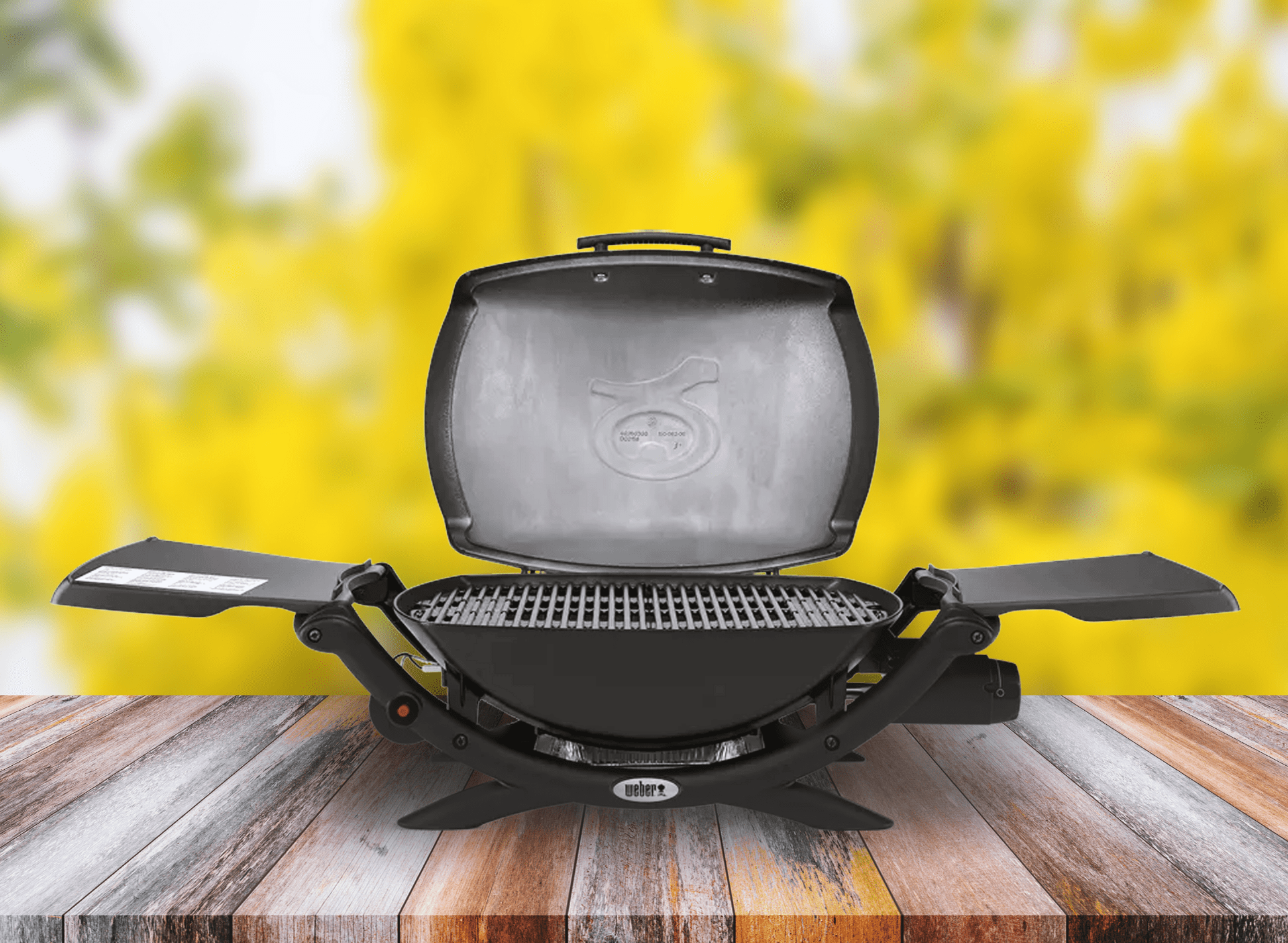 small_black_weber_barbeque_on_wooden_bench